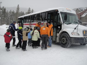 Enthusiastic children board a bus to ski school at Keystone's River Run Village.
