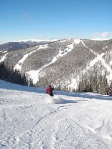 A lone skier enjoys the slopes under a bluebird sky at Keystone, Colorado.